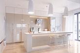 biała kuchnia, beżowa szafa z połyskiem, lampa wisząca z białym abażurem, kwadratowy okap z metalu
