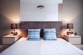 biała pościel, szare łóżko z wysokim zagłówkiem, tapeta w biało-beżowe skośne pasy