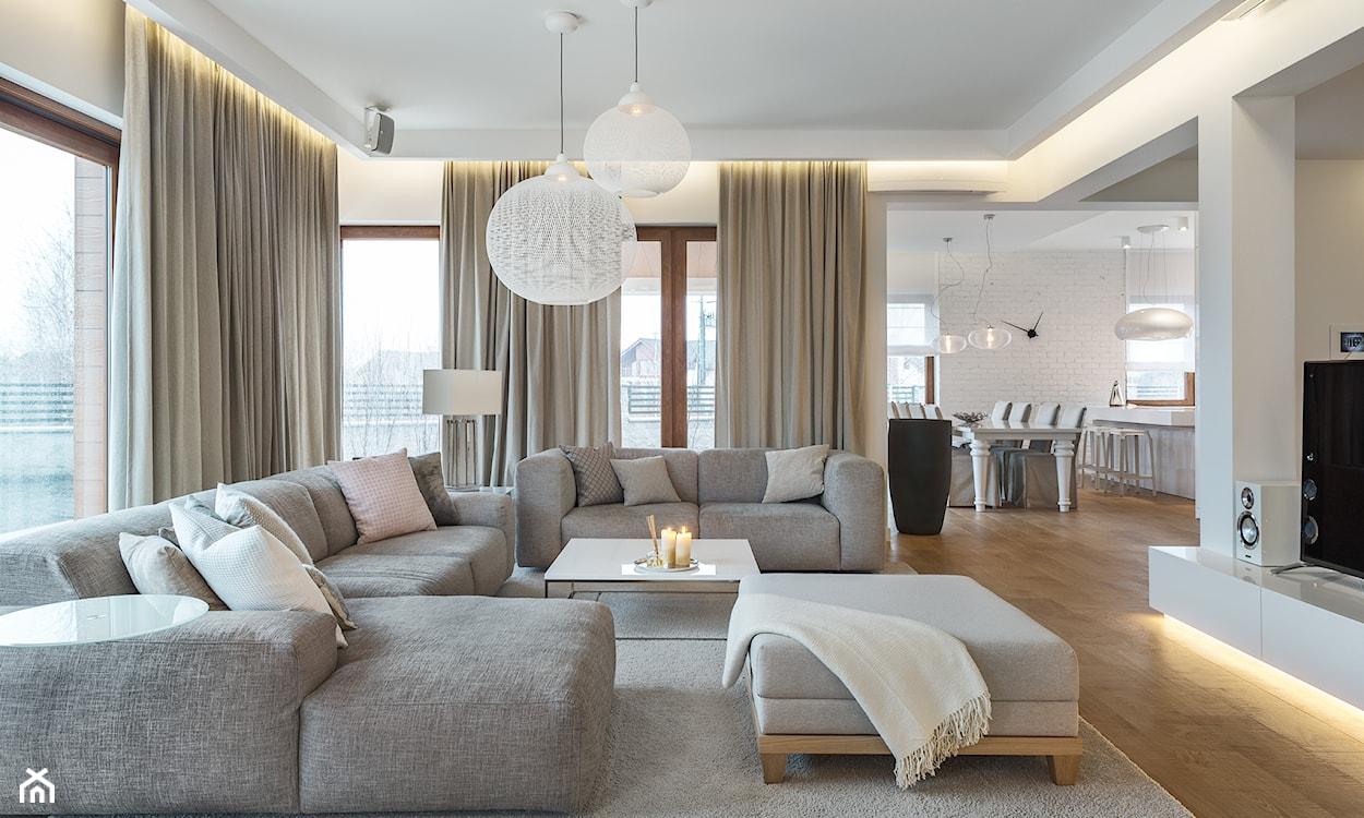 jasny salon, szara sofa narożna, beżowe zasłony, kremowy dywan, biały stolik na metalowych nogach