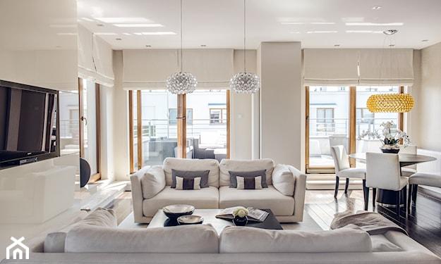 szara sofa, biała sofa, poduszka w paski, srebrna lampa sufitowa, białe rolety, złota lampa wisząca