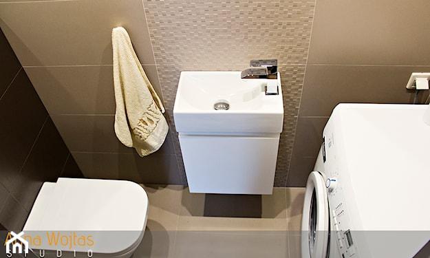 mała łazienka z pralką, beżowe płytki ścienne, kremowy ręcznik