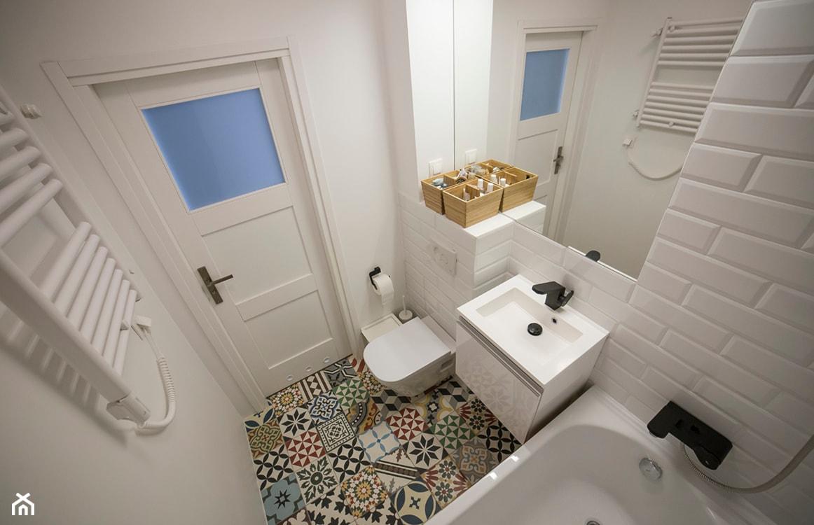 mała łazienka, gres hiszpański na podłodze, białe kafelki na ścianach