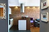 cegła naturalna, białe meble kuchenne, drewniana podłoga, metalowy okap wiszący