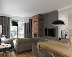 salon z kominkiem z cegły - zdjęcie od Projektownia Wnętrz