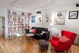 ściana z regału z książkami, czerwona sofa, grafitowa sofa, okrągły stolik, metalowa lampa podłogowa z białym abażurem