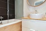 białe meble łazienkowe, czarne płytki ścienne, okrągłe lustro