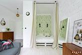 łóżko z palet za zasłoną, zielona tapeta, biała podłoga z drewna, szara sofa, drewniana komoda