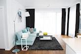 drewniana podłoga, grafitowy dywan, miętowa sofa, czarne długie zasłony, metalowa lampa podłogowa z białym abażurem
