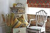 białe krzesło z obiciem w kwiaty, komoda retro, pomarańczowa roleta w romby