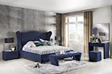 granatowe łóżko z wysokim zagłówkiem, biały dywanik, szara ściana, kremowe zasłony