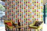 zielone fotele na metalowych nóżkach, okrągły stolik, pomarańczowa poduszka, tapeta w kolorowe wzory