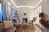 beżowe fotele i białe ściany w salonie  kominkiem