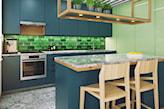 marmurowy blat, niebieskie meble kuchenne, drewniane hokery