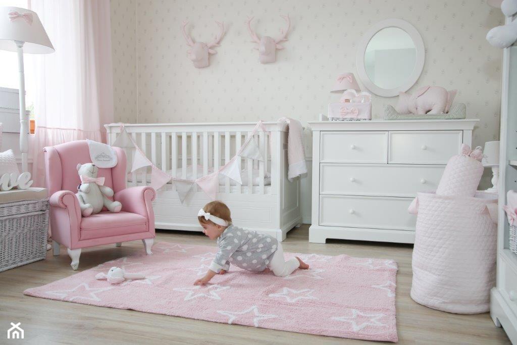 różowy fotel na białych nóżkach, biała komoda, różowy dywan w białe gwiazdki