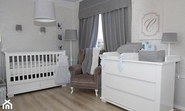 biała komoda, białe łóżeczko dziecięce, szare zasłony, szary fotel na nóżkach