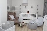 białe łóżeczko niemowlęce, beżowy fotel na nóżkach, biała ściana, szary puf