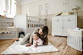 biały dywanik, drewniana podłoga, białe łóżeczko dziecięce, beżowa lamperia, plecione kosze
