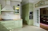 zielone meble z rzeźbionymi ozdobami, białe kafelki, kuchnia w stylu prowansalskim