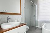 kabina prysznicowa walk in, lustro w drewnianej ramie, białe szafki łazienkowe z drewnianym blatem