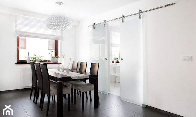 biały żyrandol, stół z ciemnego drewna w jadalni