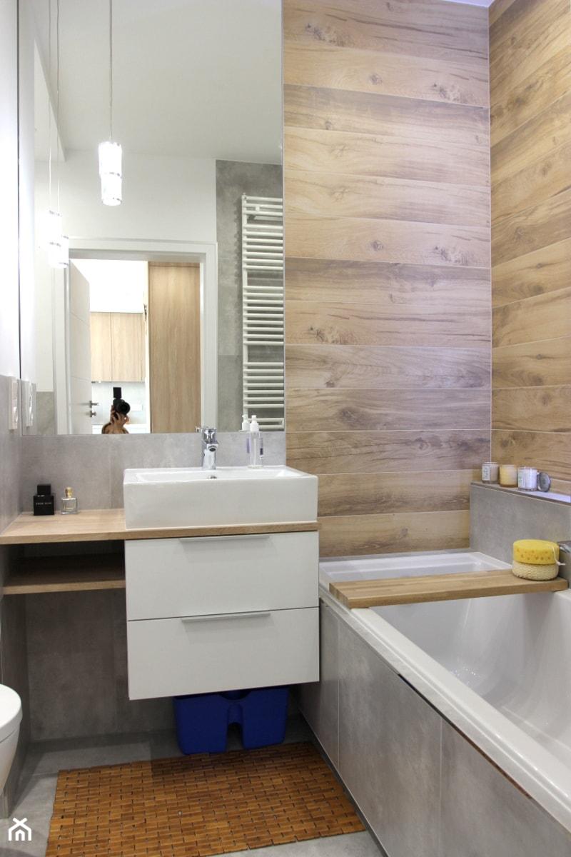Nowoczesne mieszkanie w apartamentowcu, biel i szarość ocieplane drewnem - Mała szara łazienka na poddaszu w bloku w domu jednorodzinnym bez okna, styl nowoczesny - zdjęcie od MK HOME