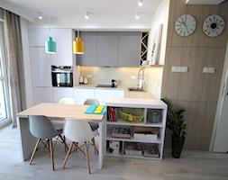 nowoczesnie, elegancko z klasą, szarosci ocieplone drewnem - Średnia biała kuchnia w kształcie litery l w aneksie z wyspą z oknem, styl nowoczesny - zdjęcie od MK HOME
