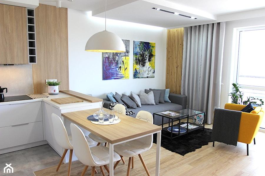 Nowoczesne mieszkanie w apartamentowcu, biel i szarość ocieplane drewnem - Mały biały salon z kuchnią z jadalnią, styl nowoczesny - zdjęcie od MK HOME