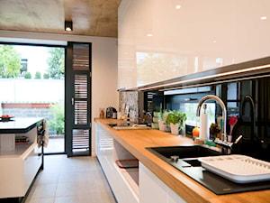 Współczesne wnętrza domu jednorodzinnego - Średnia otwarta biała czarna kuchnia jednorzędowa w aneksie z wyspą z oknem, styl nowoczesny - zdjęcie od Michał Hoffmann projektant wnętrz