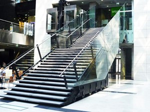 Schody w atrium biurowca Focus w Warszawieoraz szklana kładka nad wejściem głównym
