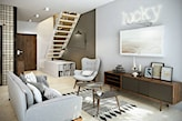 neonowy napis na ścianie, szara sofa na drewnianych nóżkach, dywan z frędzlami, drewniane schody, komoda na drewnianych nóżkach