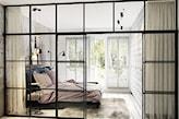 sypialnia z oryginalną szklaną ścianą ze szprosami