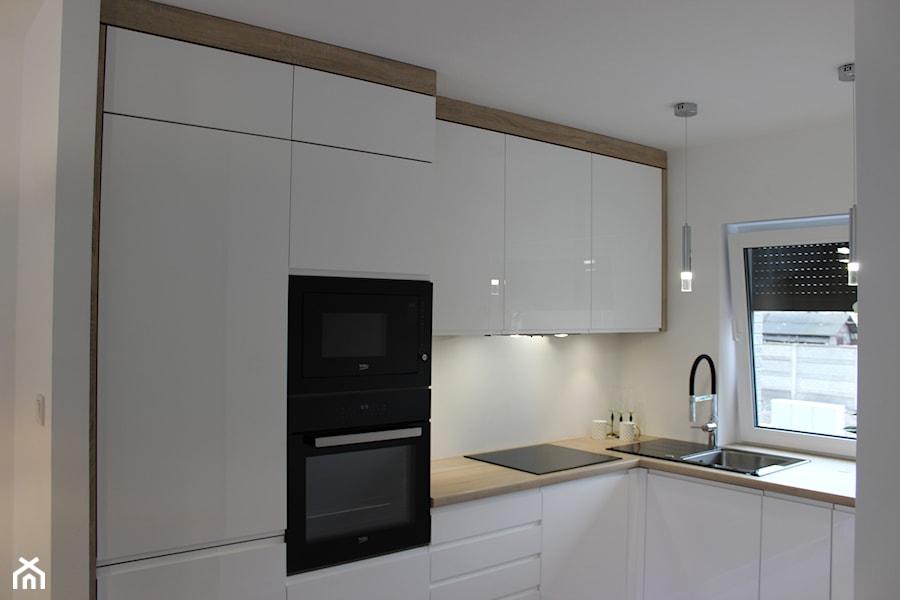 Biały lakier+Dąb Sonoma - Średnia biała kuchnia w kształcie litery l w aneksie z oknem, styl nowocz ... - zdjęcie od AJ-Strefa Kuchni
