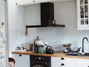 Kuchnia skandynawska z białymi meblami i czarnym okapem Globalo Nomina