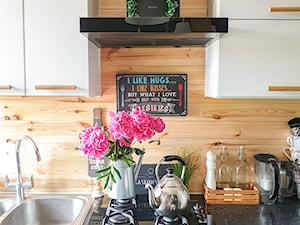 Projekt białej kuchni z elementami drewna z okapem Verta Black