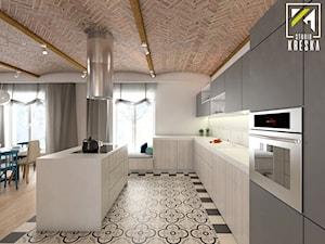 Projekt aranżacji wnętrz domu parterowego w Gostyniu pod Głogowem - Duża otwarta szara kuchnia w kształcie litery l z wyspą z oknem - zdjęcie od kreska.studio