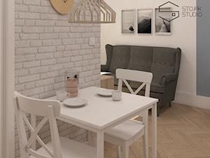 Niewielkie mieszkania na wynajem - Mała otwarta biała szara jadalnia w salonie, styl skandynawski - zdjęcie od Stojak Studio