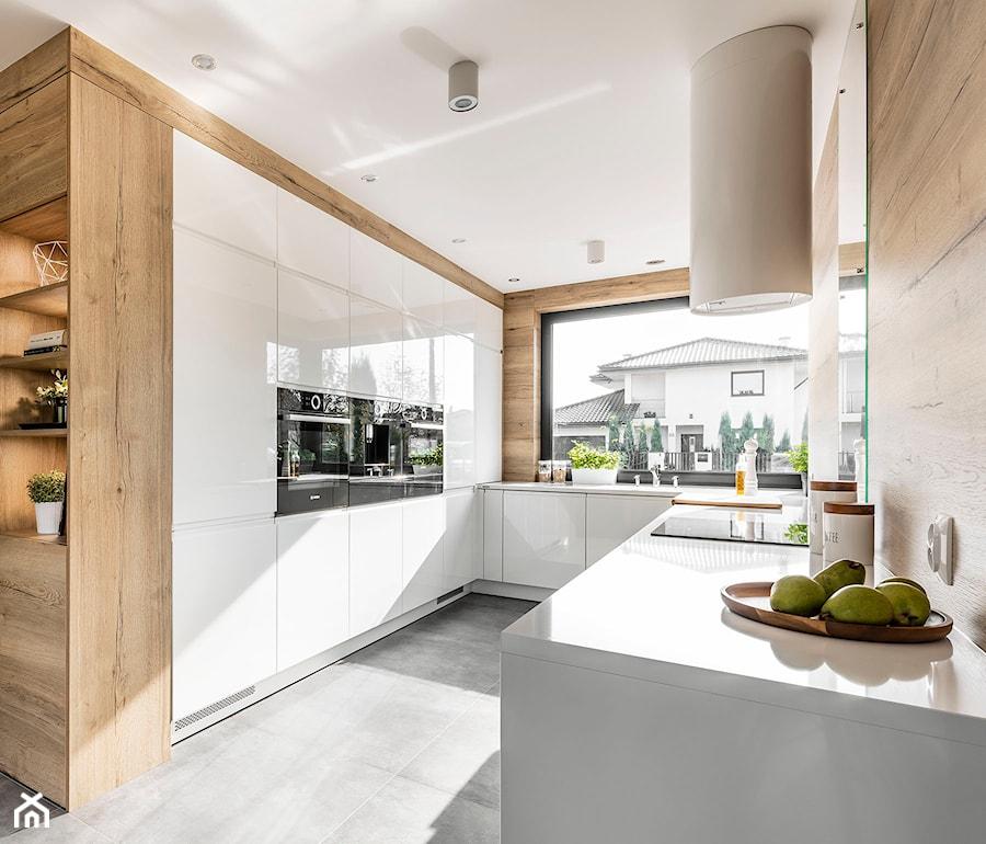 Kuchnia w Legnicy - Duża otwarta biała kuchnia w kształcie litery u w aneksie z oknem - zdjęcie od STRAŻYŃSKI STUDIO