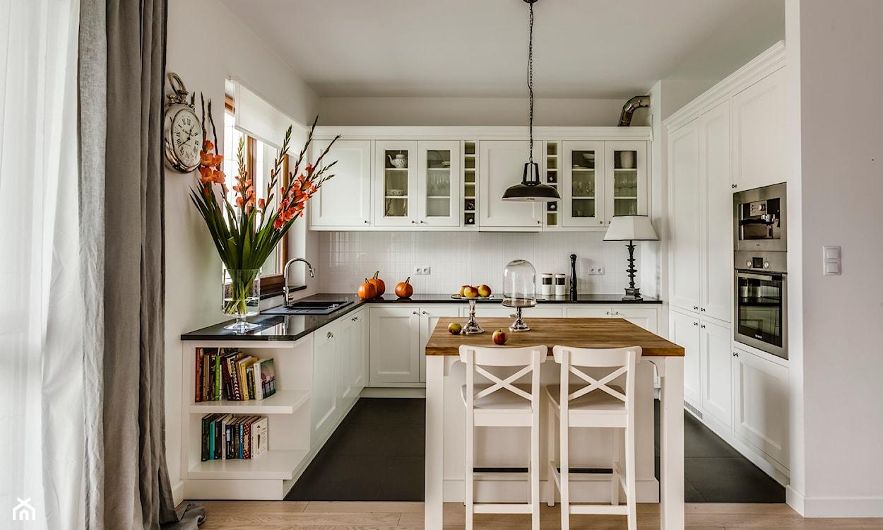 białe meble kuchenne, białe hokery, czarna lampa wisząca, metalowy zegar, szare zasłony