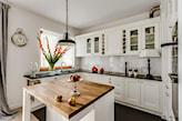 kuchnia w stylu prowansalskim, białe meble kuchenne z czarnym blatem, metalowa lampa wisząca