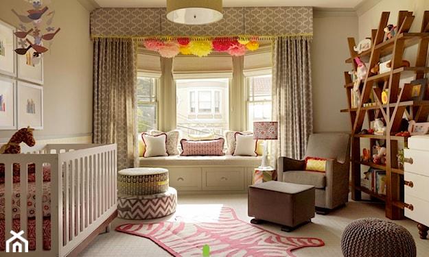 różowy dywanik w kształcie zebry, białe łóżeczko niemowlęce, brązowy puf