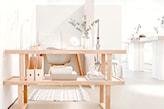 biurko z jasnego drewna, białe krzesło, białe ściany