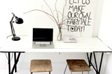 białe biurko na metalowych nogach, metalowy taboret, czarna lampa stołowa, szklany wazon