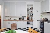 kremowe meble kuchenne z drewnianym blatem, biało-czarne płytki podłogowe, okrągły stół, drewniane krzesła