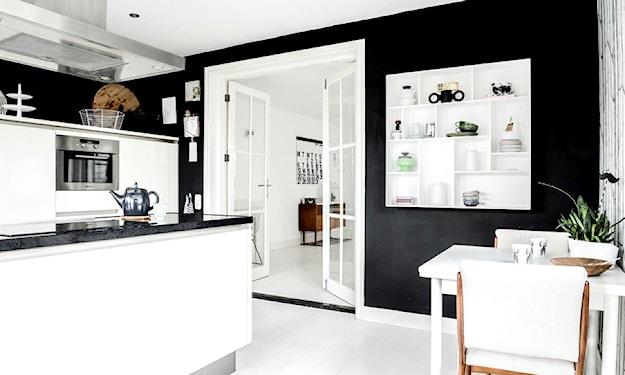 białe meble z czarnymi blatami i czarne ściany w kuchni
