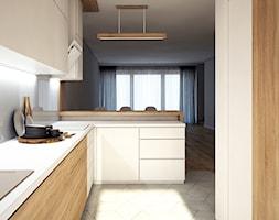 Bia%C5%82a+kuchnia+z+elementami+drewna+-+zdj%C4%99cie+od+Totius+Studio