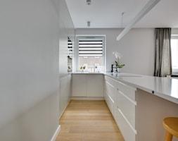Mieszkanie wg autorstwa studia KAST DESIGN z Paryża - Średnia otwarta wąska biała kuchnia w kształcie litery u w aneksie z oknem, styl minimalistyczny - zdjęcie od Radosław Sobik Fotografia
