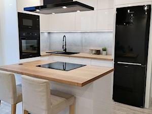 Nowoczesna biała kuchnia z czarnym AGD