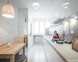 Realizacja projektu/jasno i przestrzennie - Średnia zamknięta wąska biała kuchnia dwurzędowa, styl skandynawski - zdjęcie od MANUstudio • projektowanie wnętrz