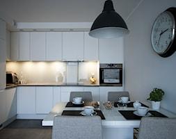 Realizacja - Czysty minimalizm - Średnia otwarta biała kuchnia w kształcie litery l w aneksie, styl nowoczesny - zdjęcie od WOJSZ studio