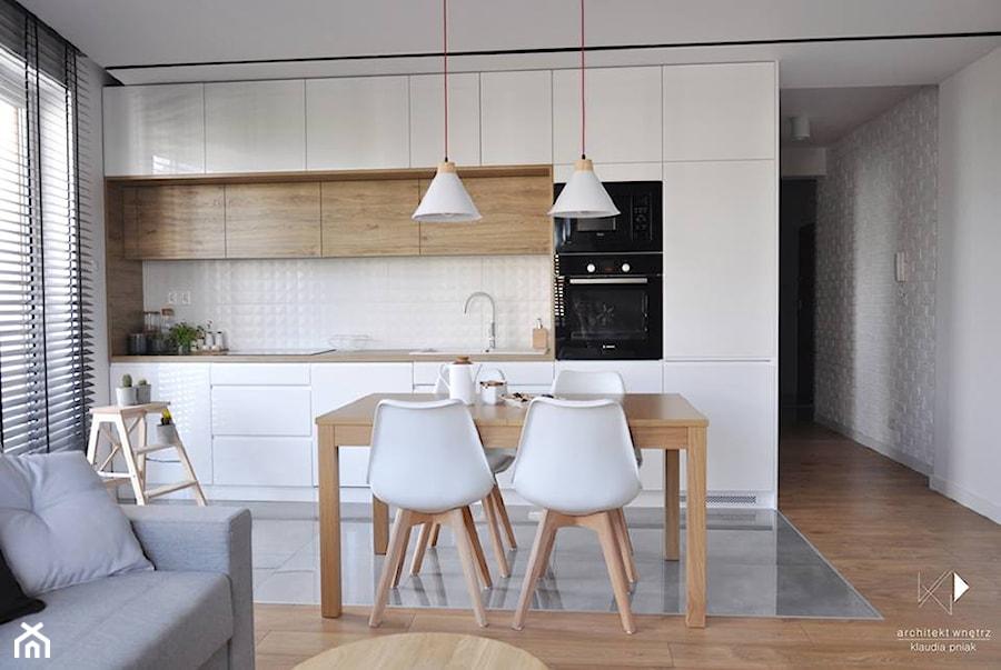 Mieszkanie Kraków,50m2. Realizacja - Mała otwarta biała szara jadalnia w kuchni w salonie, styl nowoczesny - zdjęcie od STUDIO PNIAK